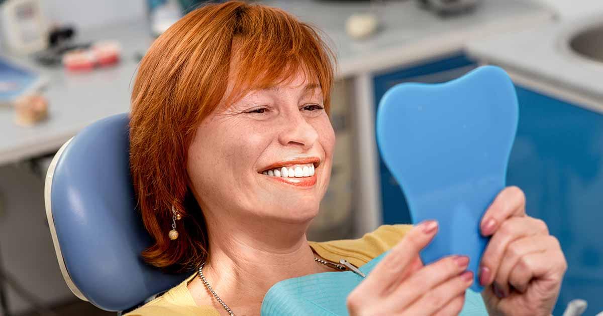 Woman smiling at teeth while at dentist