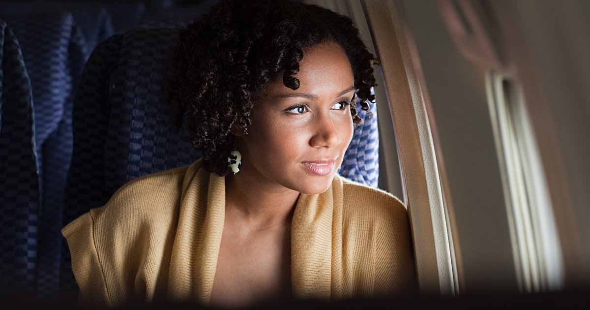 Woman looking out plane window