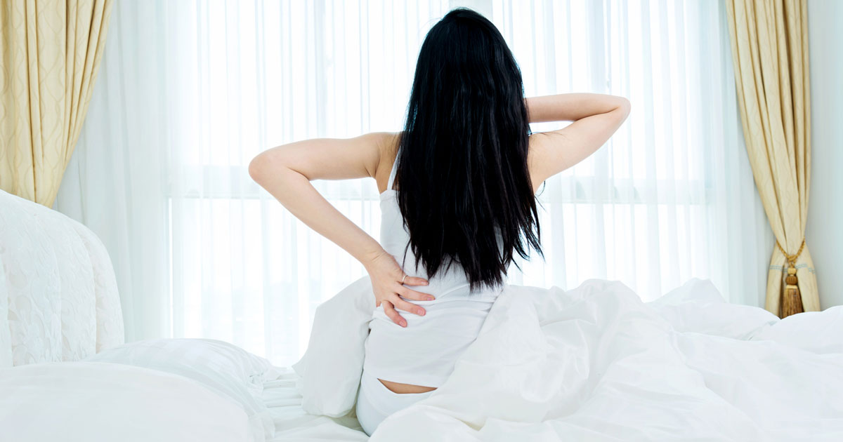 Woman sitting in bed stretching her back