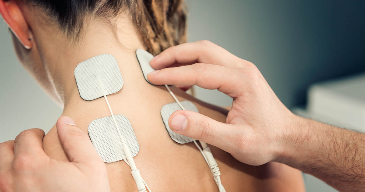 TENS unit on the back of woman's neck