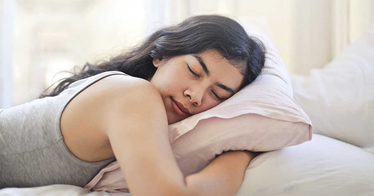 a woman sleeping on a bed with a pillow